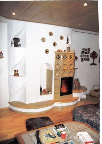 Warmluftofen mit Feuersicht (HKD 1), eingebaut in früheren Türdurchbruch mit Holzlager und künstlerischen Fächern. 1992
